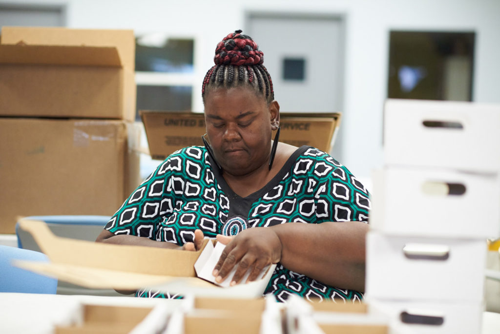 Lady assembling cardboard boxes