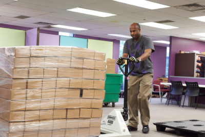 Man moving boxes using a dolly