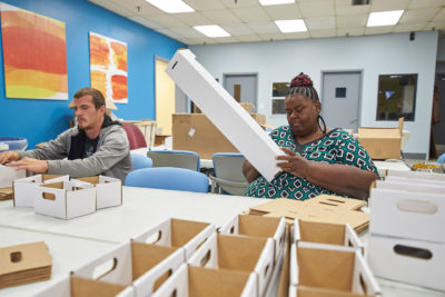 2 people folding boxes
